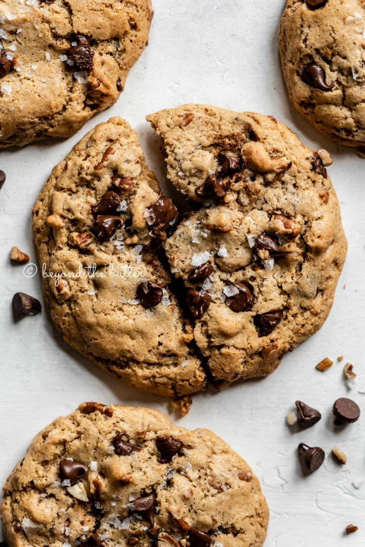 Overhead image of almond butter chocolate chip pecan cookies with the center cookie splitting in two | All images © Beyond the Butter™