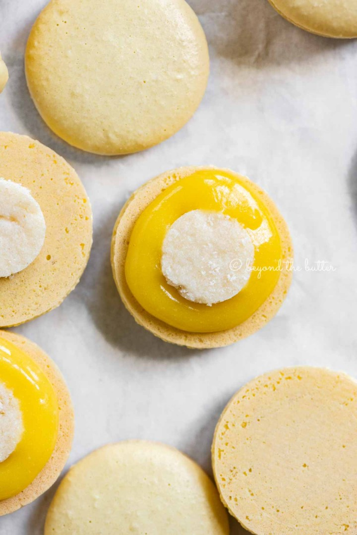 Angled image of lemon bar macarons half opened topped with shortbread crust centers and lemon curd filling | All Images © Beyond the Butter™