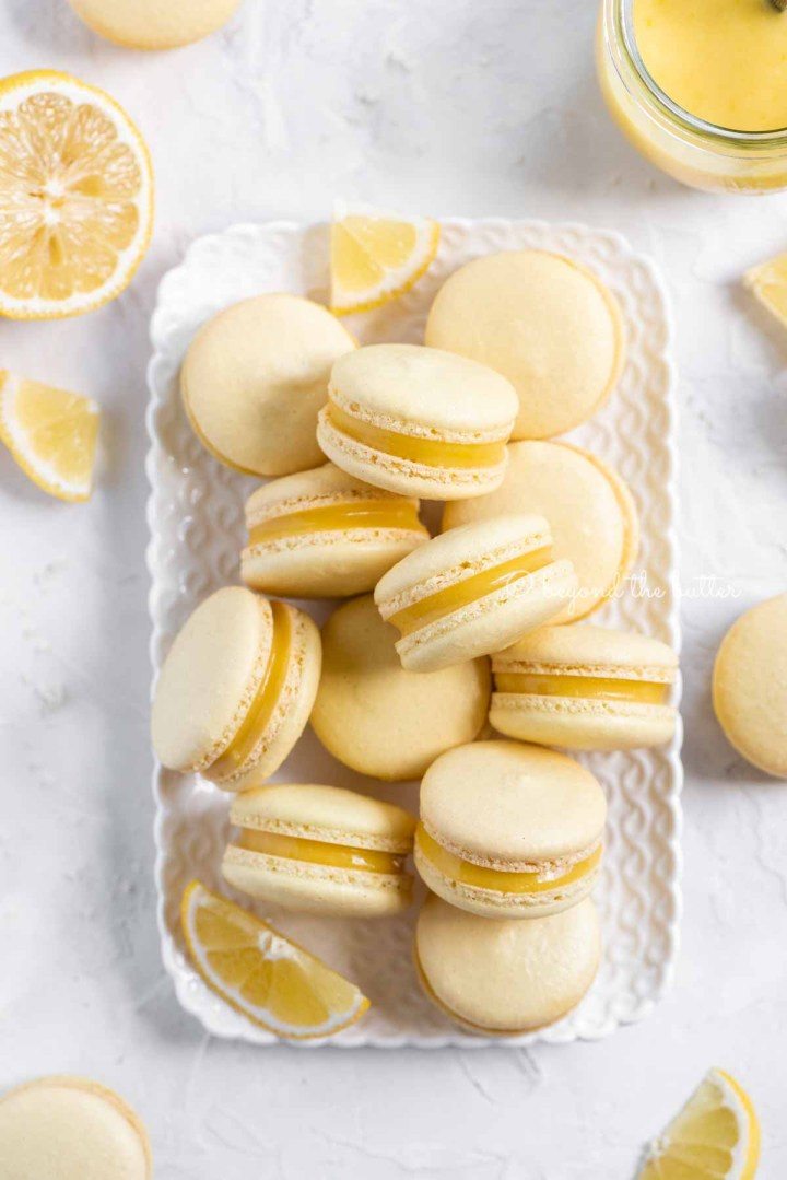 Overhead image of lemon bar macarons on a white dessert tray with lemon wedges | All Images © Beyond the Butter™