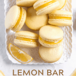 Pinterest image of lemon bar macarons on a white dessert tray with lemon wedges | All Images © Beyond the Butter™