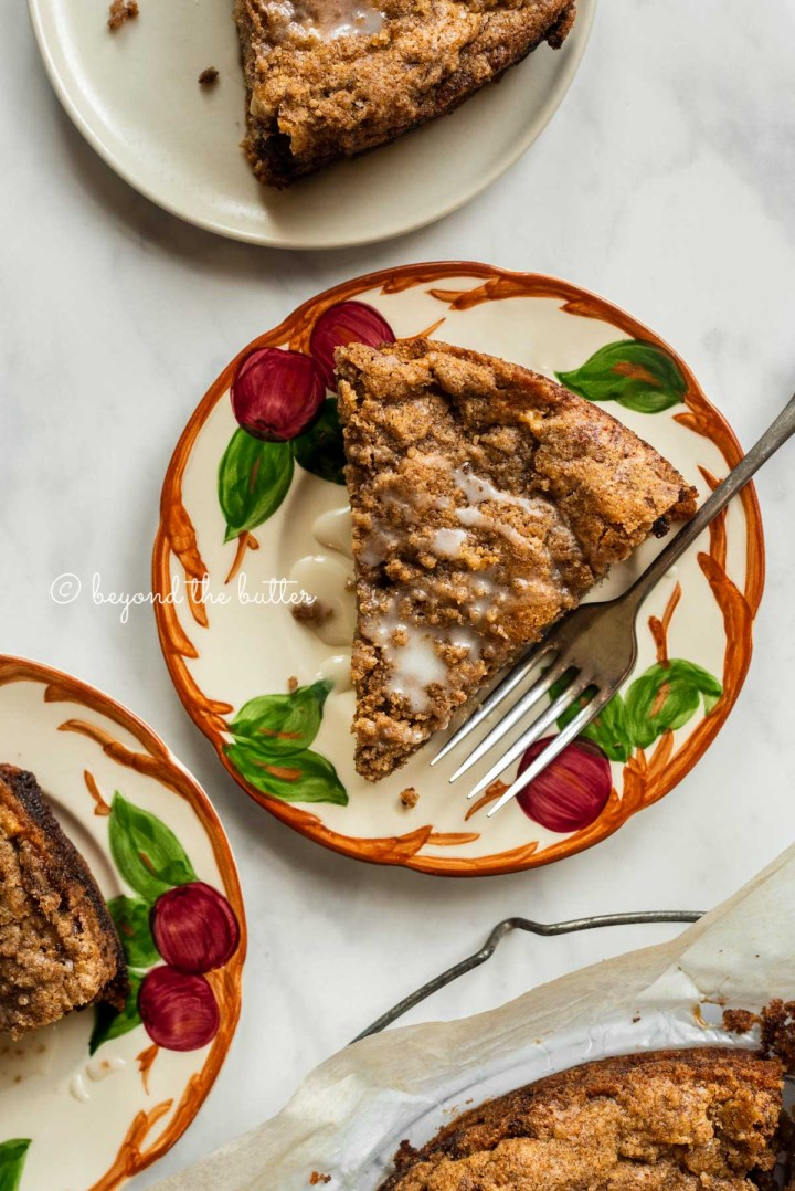 Slices of warm apple coffee cake on dessert plates drizzled with a simple vanilla glaze | All Images © Beyond the Butter™