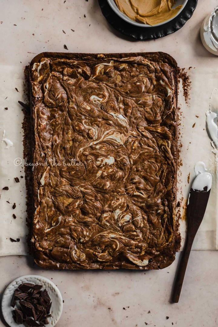 Uncut marshmallow peanut butter brownies on parchment paper and bowl of marshmallow fluff and spreader tool beside it | All Images © Beyond the Butter™