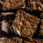 Closeup of randomly placed marshmallow peanut butter brownies on parchment paper | All Images © Beyond the Butter™