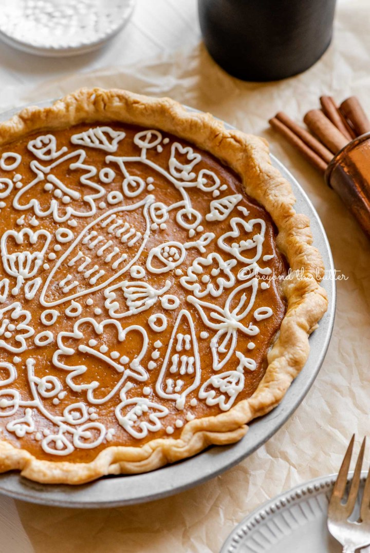 Angled image of pumpkin pie with a piped cream cheese frosting decoration surrounded by forks, cinnamon sticks, plates, and small pitcher of milk | All images © Beyond the Butter™