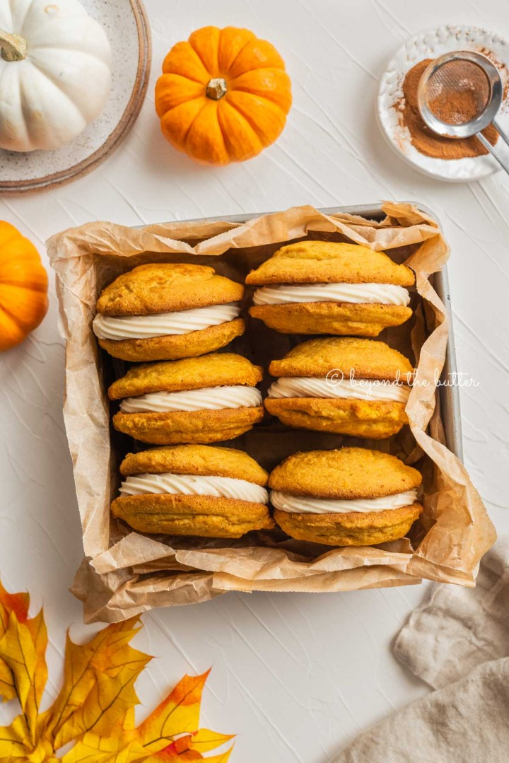 Overhead image of pumpkin whoopie pies in parchment paper lined baking tin on white background with mini pumpkin, fall leaves, dessert plates, and napkin around them | All Images © Beyond the Butter™