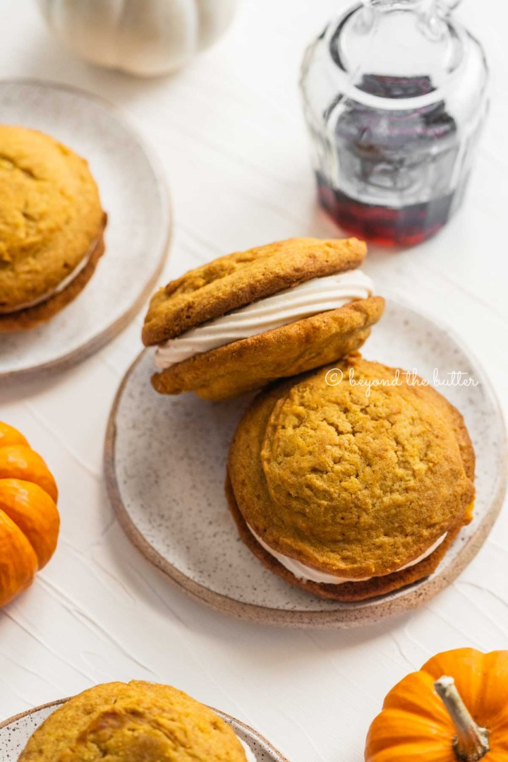 Pumpkin whoopie pies on speckled dessert plates with randomly placed mini pumpkins and a glass of maple syrup | All Images © Beyond the Butter™