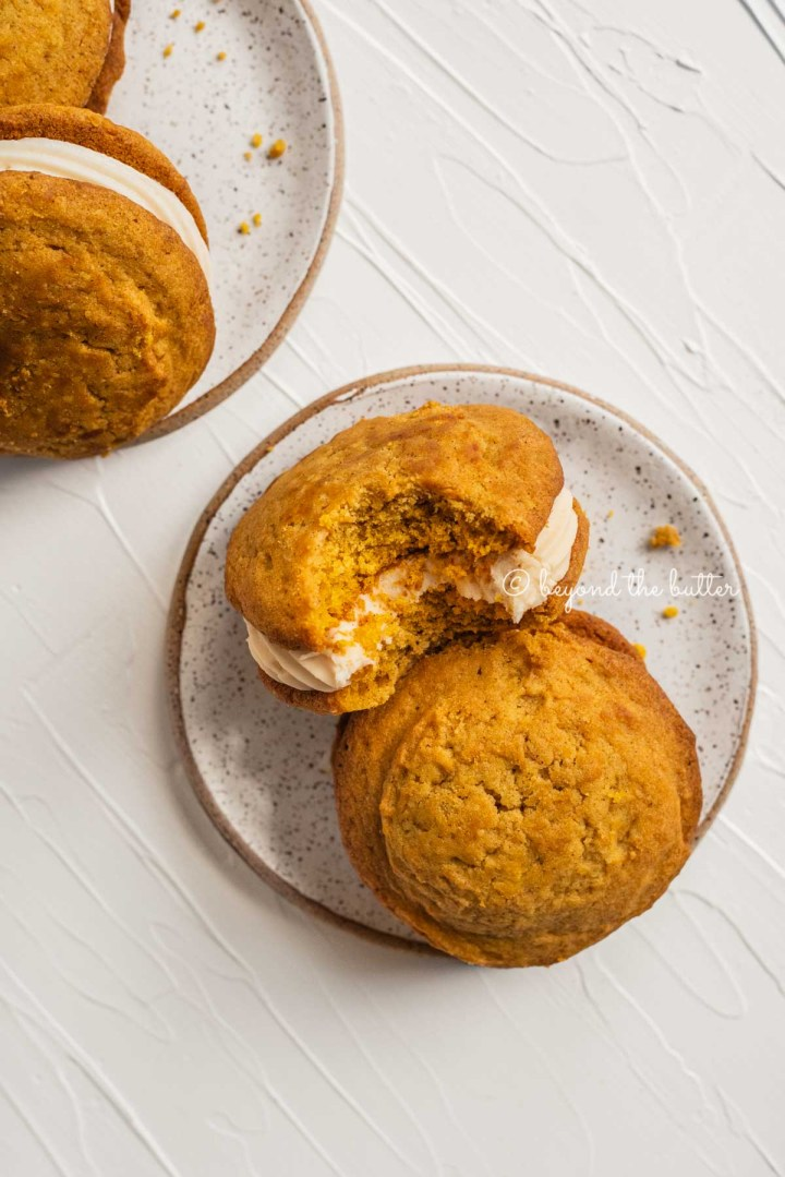Pumpkin whoopie pies with one half eaten resting on 2 speckled dessert plates | All Images © Beyond the Butter™