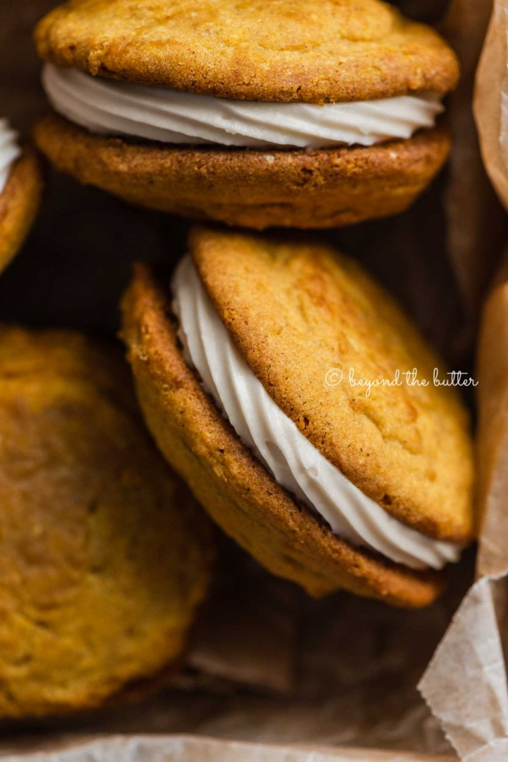 Overhead close up image of randomly placed pumpkin whoopie pies in parchment paper lined baking tin | All Images © Beyond the Butter™