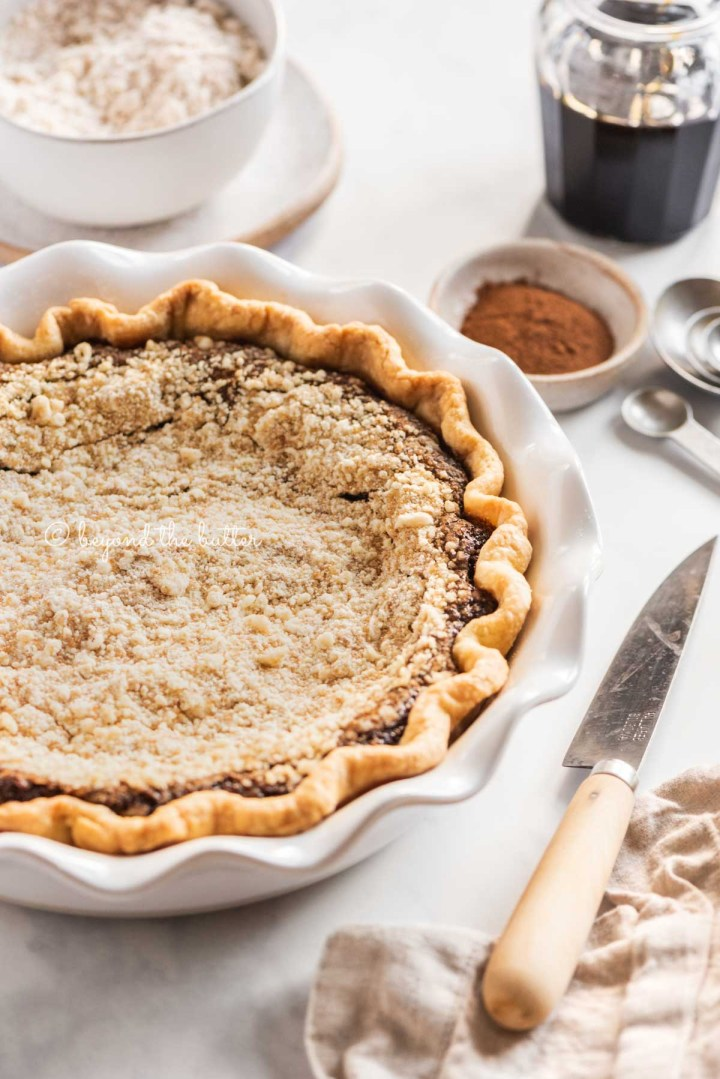 pie plate with uncut shoo fly pie with bowls of crumb topping and cinnamon above and a knife, measuring spoons, and molasses | All Images © Beyond the Butter™