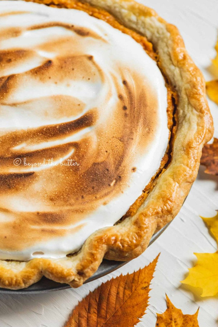 Angled close up of brown sugar sweet potato pie with toasted marshmallow meringue complimented by colorful fall leaves | All Images © Beyond the Butter®
