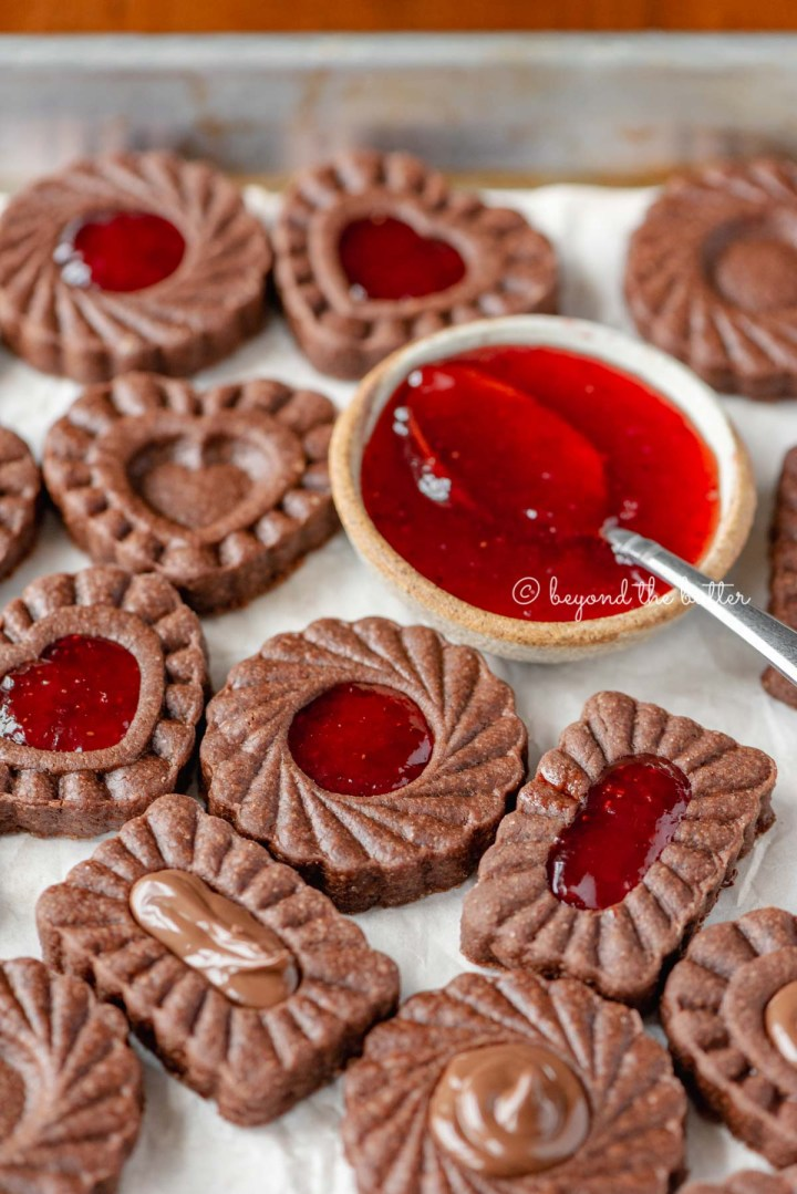 Parchment lined baking sheet full of chocolate thumbprint cookies with small bowl of strawberry jam and spoon | All Images © Beyond the Butter®