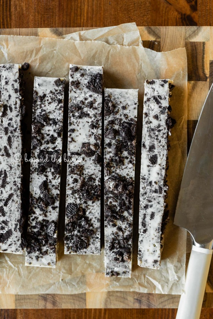 Bars of cookies and cream fudge on brown parchment paper and wood cutting board with knife on top | All Images © Beyond the Butter®