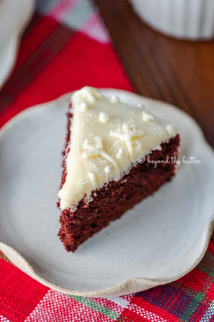 Slice of red velvet cake with cream cheese frosting on a scalloped edge dessert plate with red plaid background | All Images © Beyond the Butter®