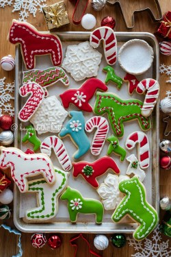 Randomly placed decorated cut out sugar cookies on a parchment lined baking sheet with ornaments and cookie cutters around it | All Images © Beyond the Butter®