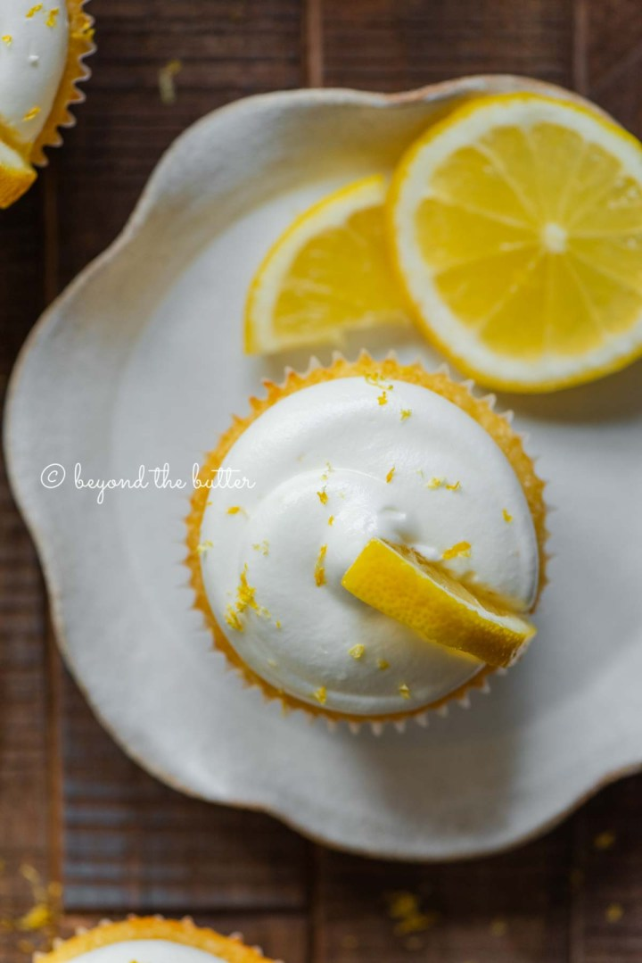 Lemon cupcake with lemon cream cheese frosting garnished with lemons on a small wavy dessert plate | All Images © Beyond the Butter®