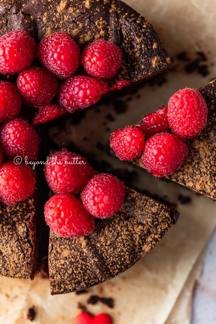 Sliced small flourless chocolate cake topped with cocoa powder and fresh raspberries on parchment paper | All images © Beyond the Butter®