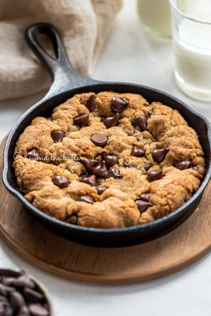 Just baked chocolate chip skillet cookies on light gray background with small bowl of chocolate chips, glasses of milk, and cloth napkin | All Images © Beyond the Butter®