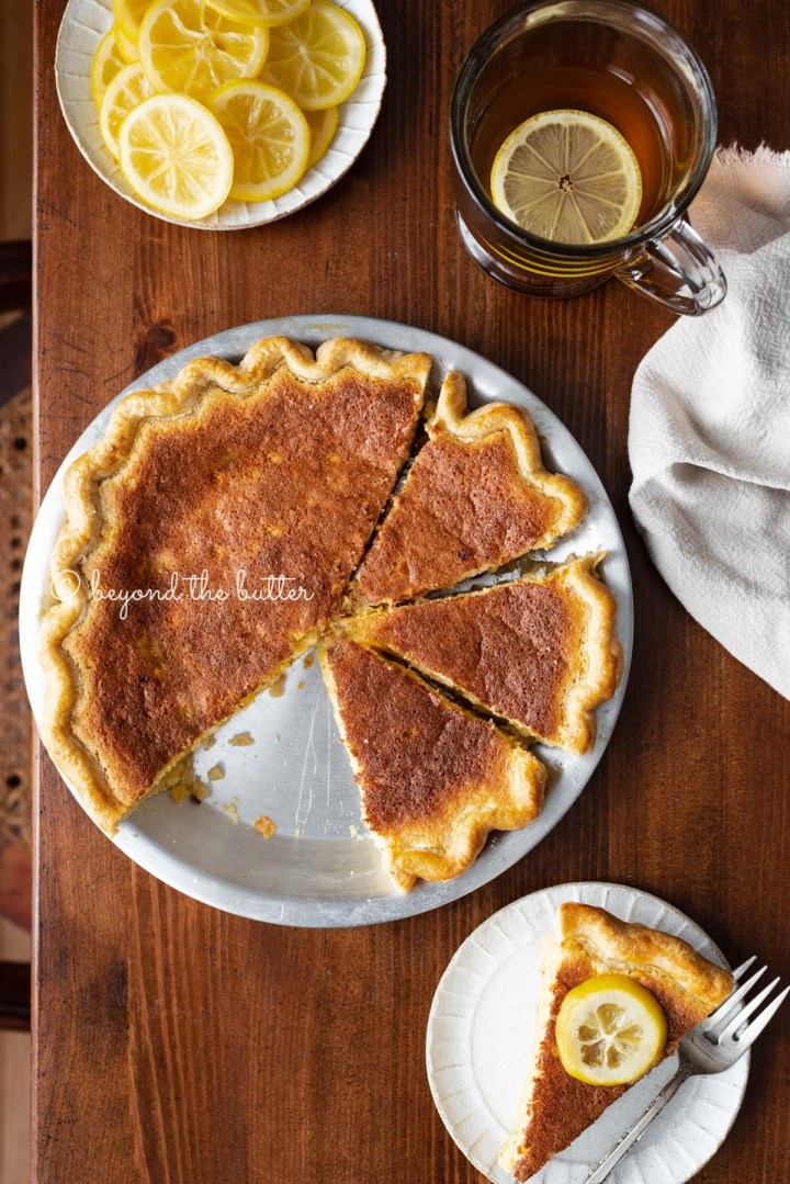 Lemon sponge pie with cut slices on dark wood background with hot lemon tea, small plate of sliced lemons, and slice to the side | All images © Beyond the Butter®