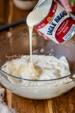 Pouring Eagle Brand® sweetened condensed milk into the mixing bowl with cream cheese | All images © Beyond the Butter®
