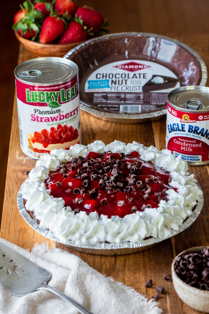 Diamond of CA® chocolate nut pie crust, Lucky Leaf® strawberry pie filling, and Eagle Brand® sweetened condensed milk with decorated no bake strawberry chocolate pie with small bowl of chocolate curls and strawberries on wood table | All images © Beyond the Butter®