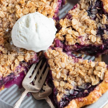 Slices of blueberry crumble pie in pie plate with scoopy of ice cream in the center | © Beyond the Butter®