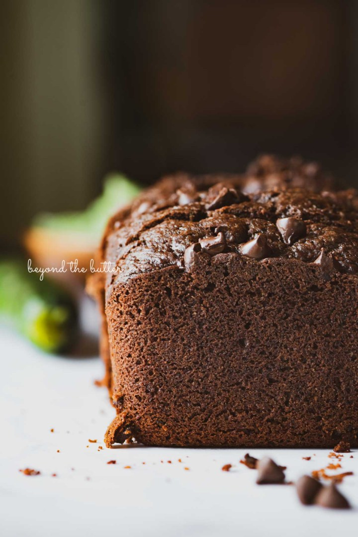Sliced chocolate zucchini bread with fresh zucchini in the background | © Beyond the Butter®