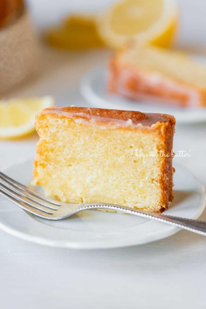 Single slice of glazed lemon cream cheese pound cake on a white dessert plate | © Beyond the Butter®