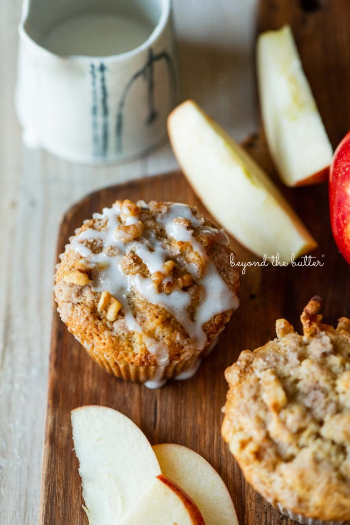Warm apple cinnamon streusel muffins on a wood cutting board with slices of apples and vanilla glaze | © Beyond the Butter®