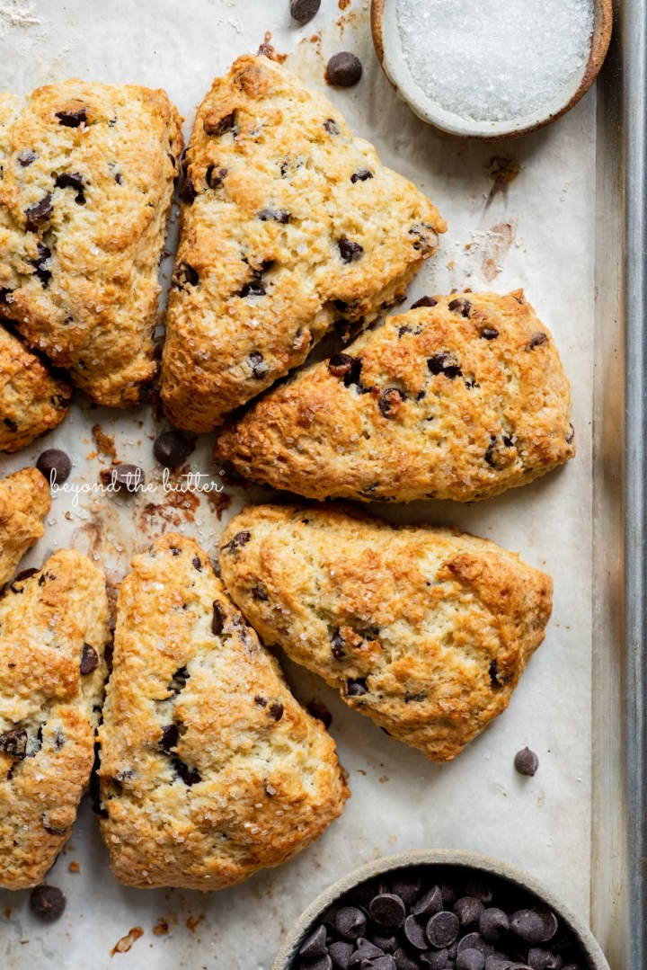 Easy chocolate chip scones on a parchment paper lined baking sheet with a bowl of chocolate chips and sparkling sugar   © Beyond the Butter®
