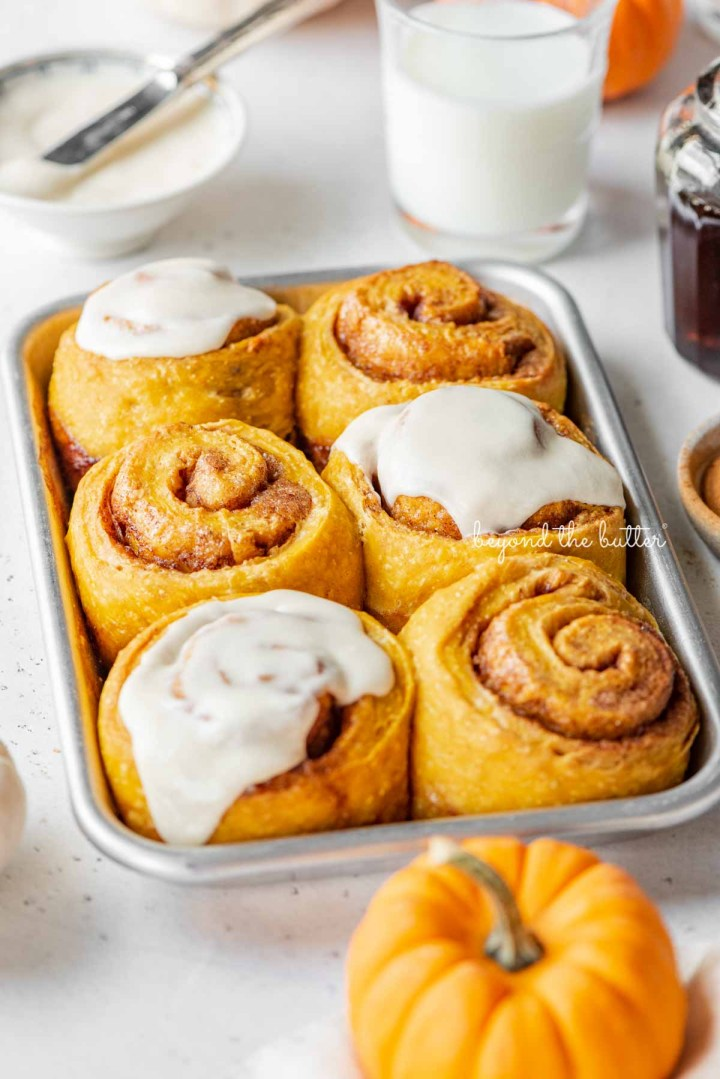 Small baking sheet of pumpkin cinnamon rolls placed by small bowl of spices, maple syrup, and pumpkins | © Beyond the Butter®