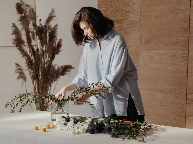 woman-in-white-robe-holding-white-flowers-4270172