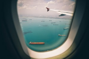 A view of ocean boats from inside a plane