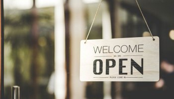 Shop door sign saying Welcome we are open - Reopening a business after lockdown