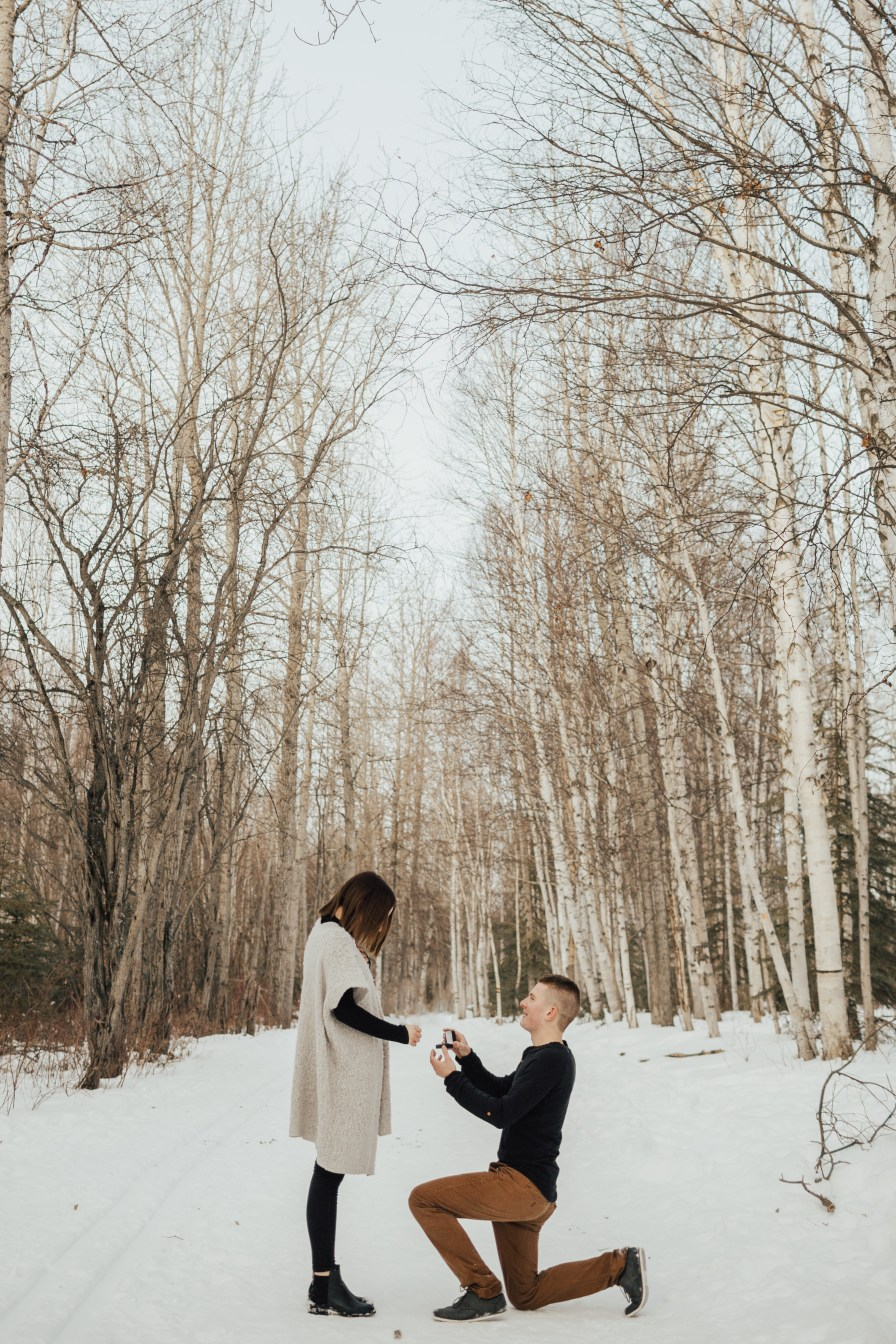 Down on one knee proposing with a ring box.