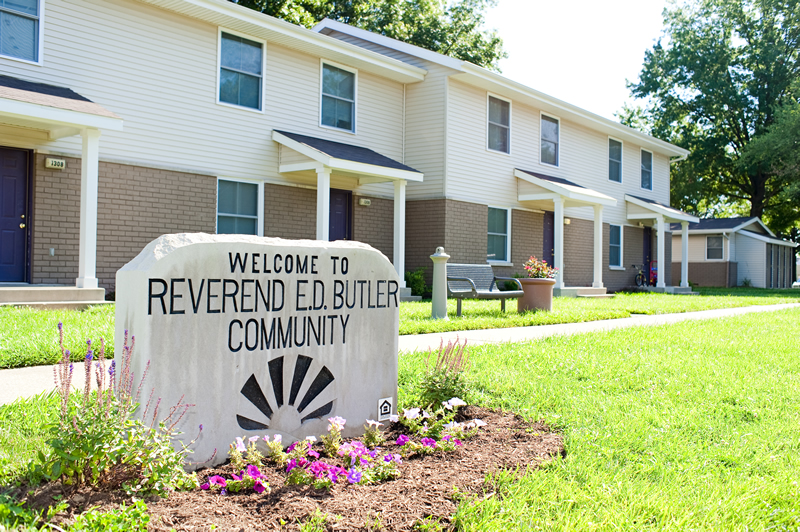 An image of the Reverend E.D. Butler Community sign, with purple flowers in front and several housing units behind.