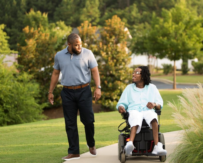 Photo of Daryl Harris walking alongside a companion in an electric wheelchair on an outdoor paved trail in Birmingham, Alabama.