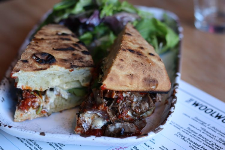 The braised beef sandwich: Tomato jam, pecorino, caramelized onions, arugula, garlic and peppercorn aioli. (Photo by Christine Hull for Bham Now)