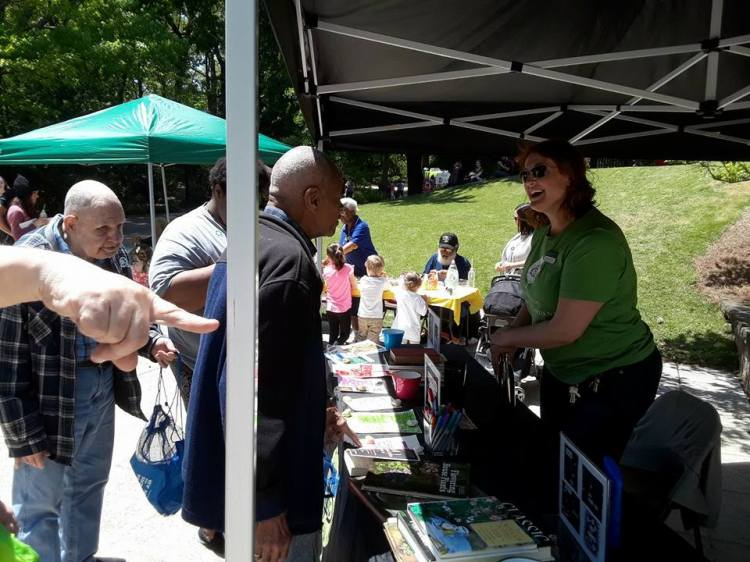 Two older gentlemen visit with a Birmingham Botanical Gardens representative at a previous Earth Day event