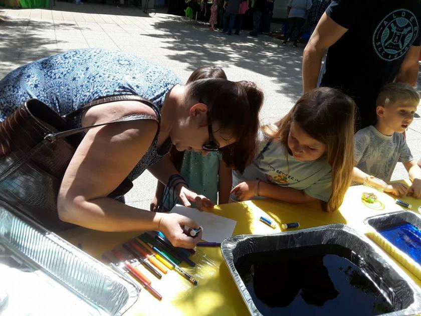 Photo shows a mother and daughter on the ground, working on an art activity for Earth Day at Birmingham Botanical Gardens in Alabama
