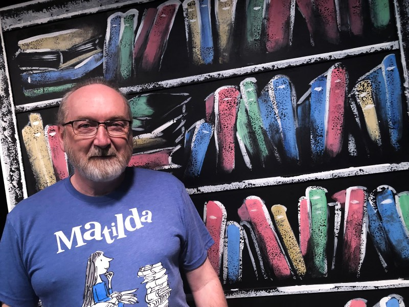 Michal Flowers stands in front of school set for Matilda the Musical.