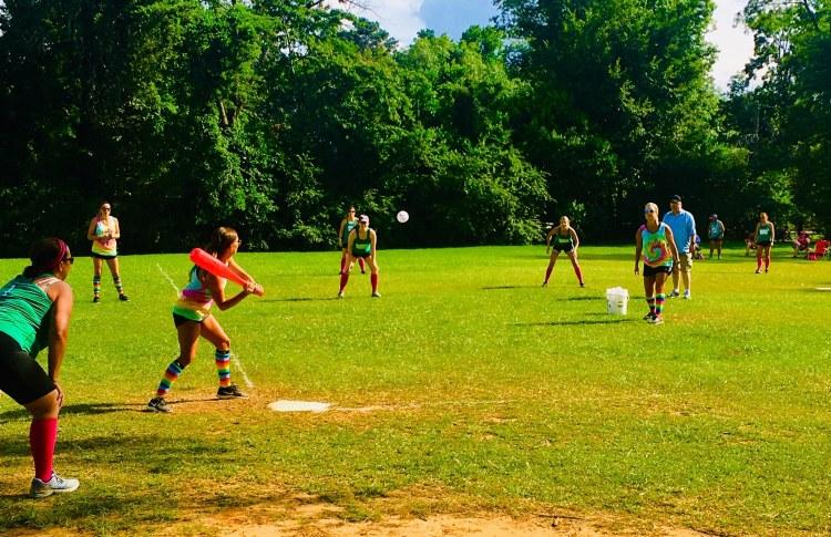 Women playing wiffle ball on a field - community sports in Birmingham