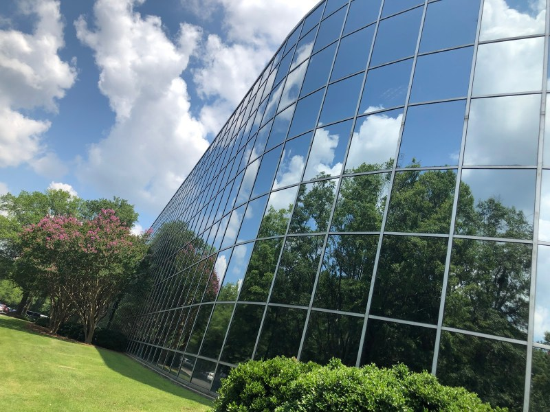 Glass walled building with sky and clouds reflection