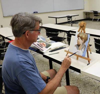 Man painting picture of a boy at  Samford Academy of the Arts