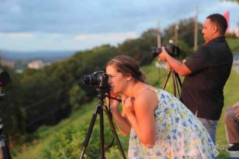 Lady looking into camera that is on a tripod on a landscape photography workshop by Samford Academy of the Arts