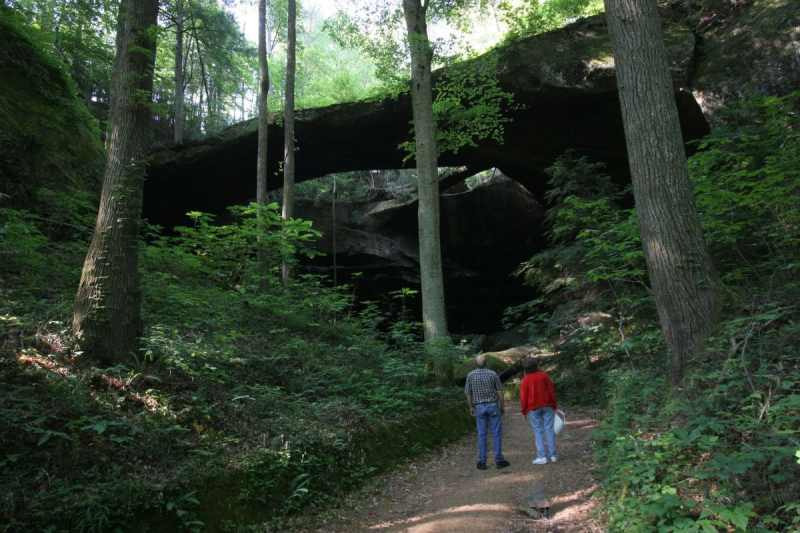 A man and woman looking at The Natural Bridge of Alabama in Winston County