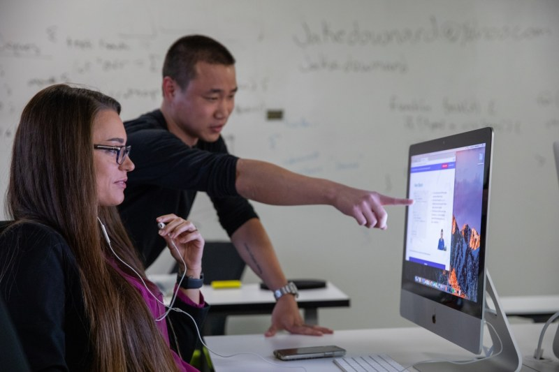 A male instructor helps a female student with an assignment on her computer.