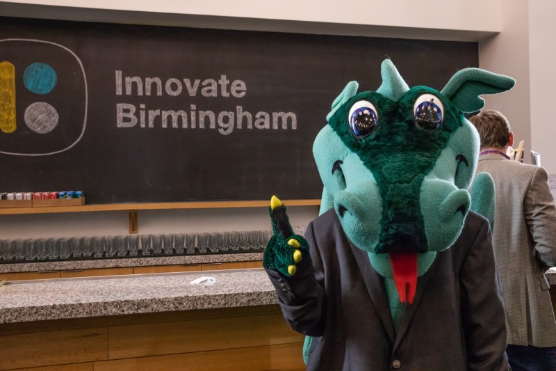 The University of Alabama Birmingham's mascot Blaze the Dragon is posing in front of Innovate Birmingham's logo. He is holding up the hand sign for #1.