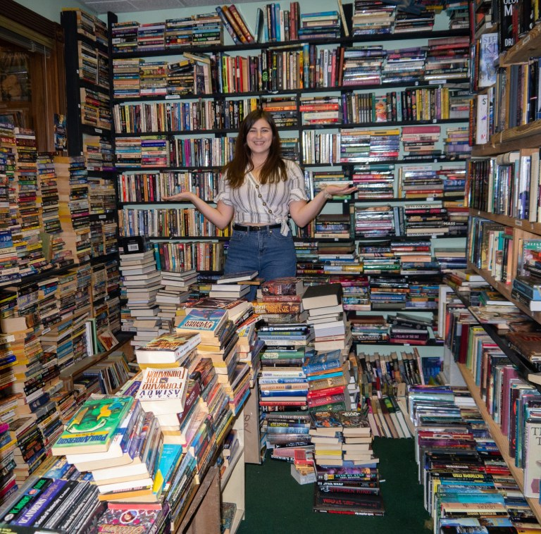 Girl Stands in Room of Books