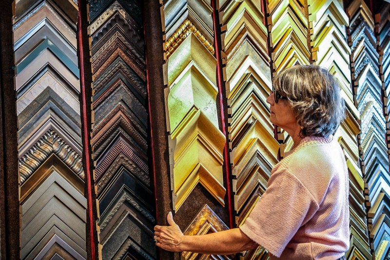 Four Corners Gallery's CEO Carla Hamilton moves panels that display framing options.