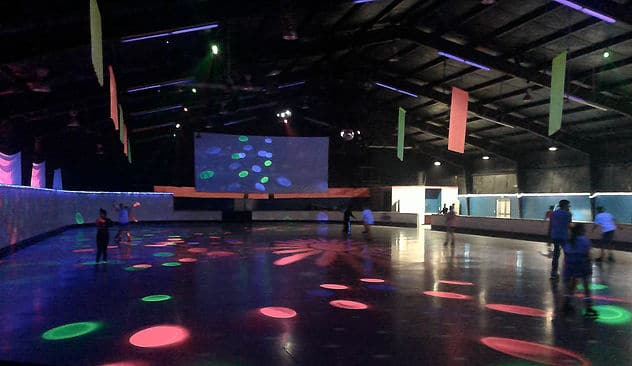 People skate around roller rink
